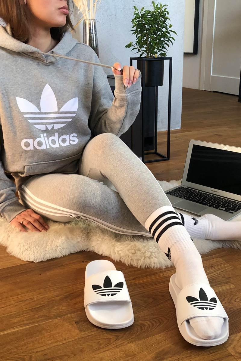 Klapki białe adidas, skarpety długie adidas i szare dresy dla niej