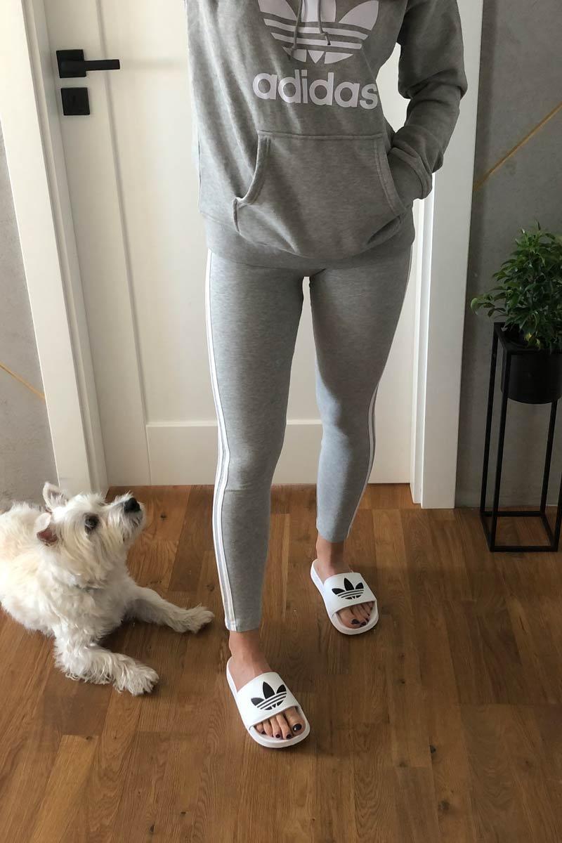 Klapki białe adidas, szare legginsy i bluza z kapturem adidas damska